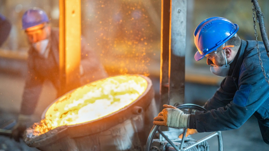 Red-hot molten steel being poured by two steel workers.