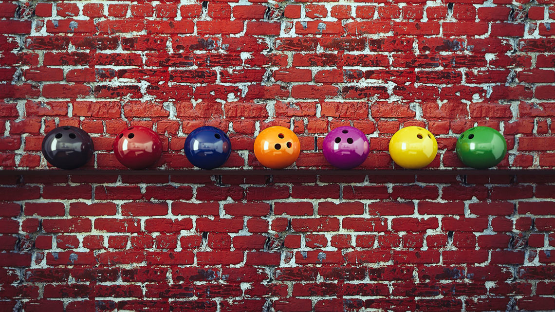 Bowling balls hanged on red brick wall with shelf
