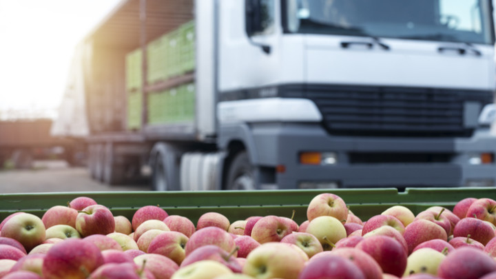 Fruit and food distribution. Truck loaded with containers full of apples ready to be shipped to the market.