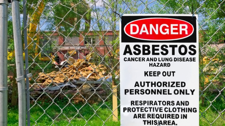 Posted asbestos sign on fence surrounding demolition of old building