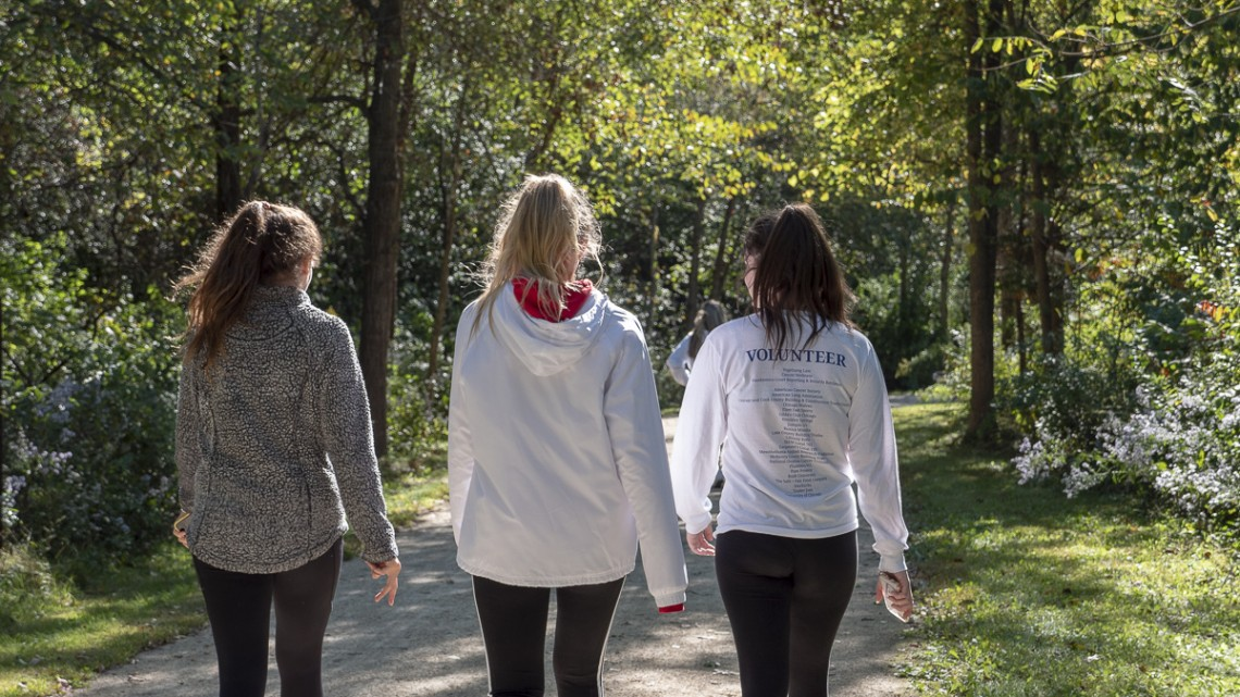 Three girls who participated in the MRFJ 5K in 2018 walking down a trail with their backs turned to the camera.