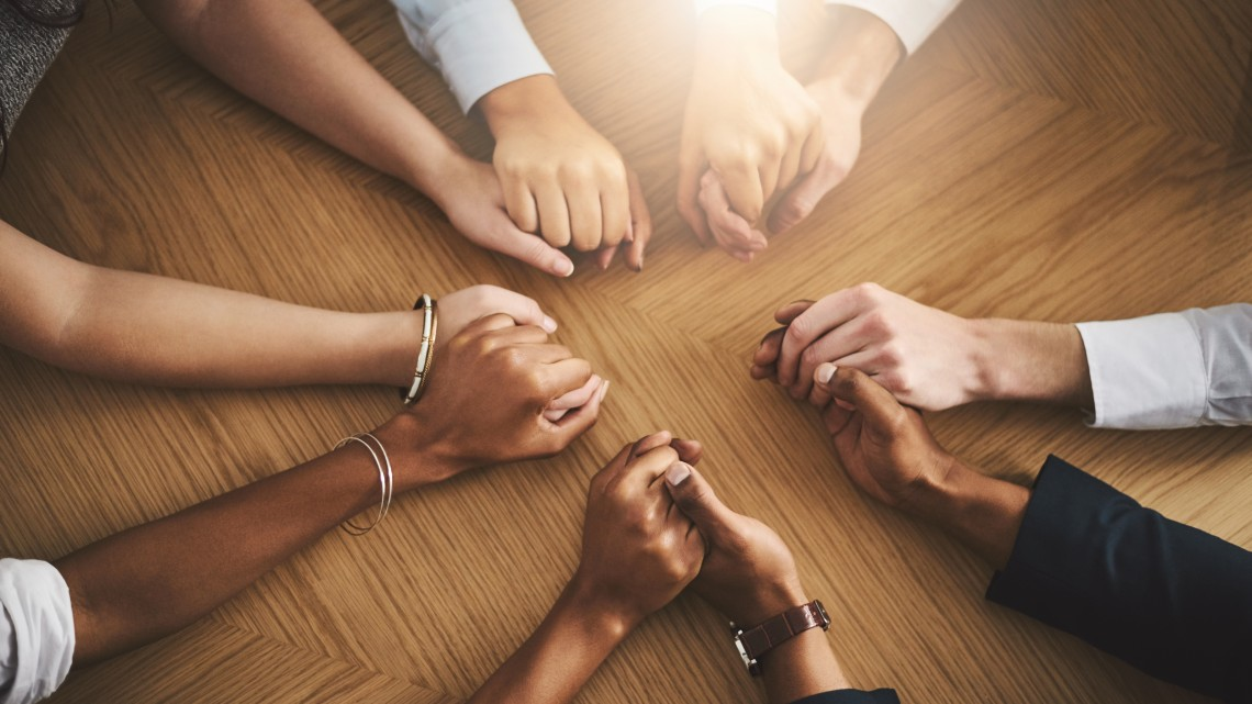 Closeup shot of a group of people sitting together at a table and holding hands.