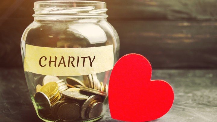 "Glass jar with the word ""charity"" written on tape and a red heart next to it."
