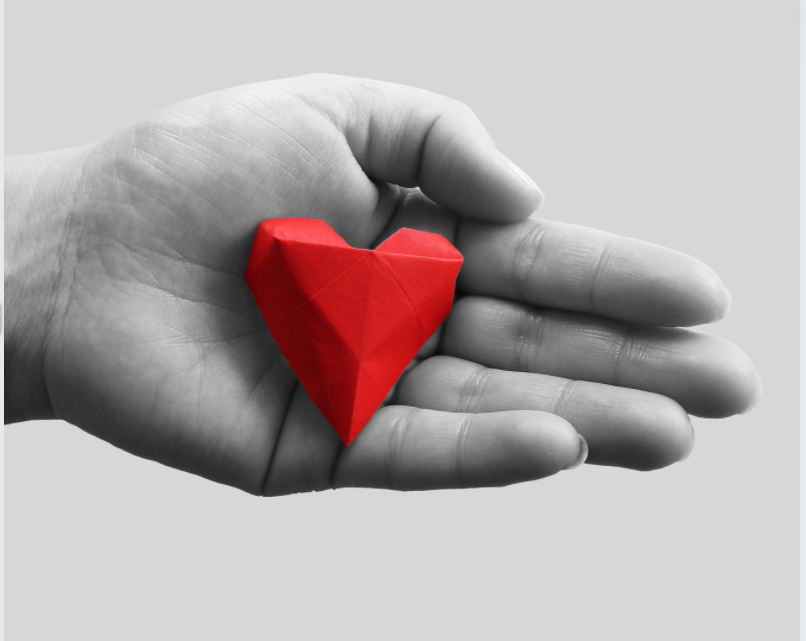 Black and white image of a red heart in someone's hand