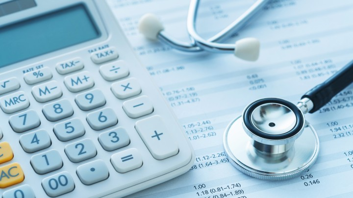 A calculator and stethoscope sitting atop a series of bills