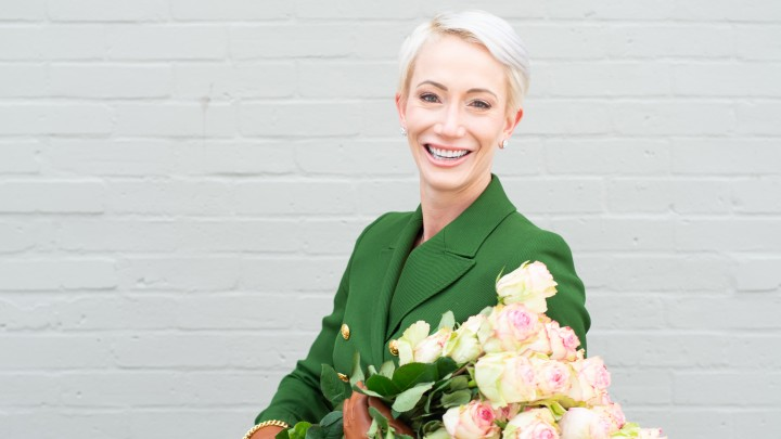 Caylei Vogelzang wears a green pant suit and smiles as she holds a bouquet of fresh long-stem light pink roses.