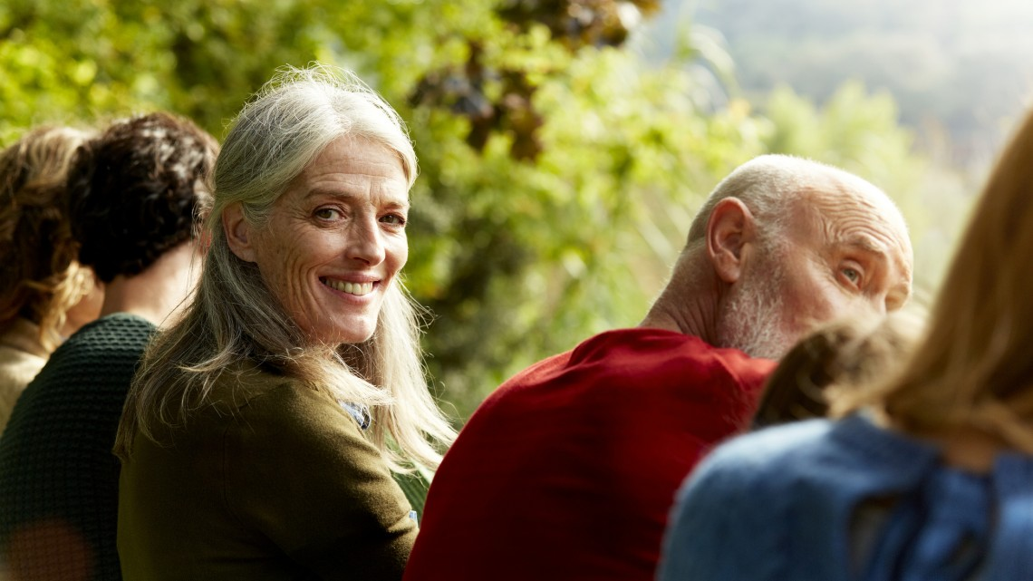Portrait of smiling senior woman sitting with family at park