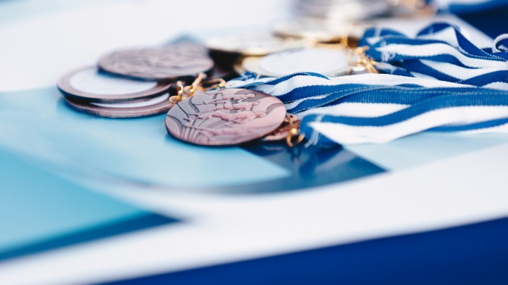 A bunch of marathon finisher's medals lying on certificate. Race running medals from marathon on blue background.